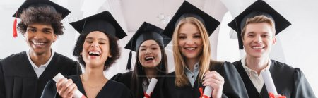 Photo for Multiethnic students in caps holding diplomas and smiling at camera, banner - Royalty Free Image