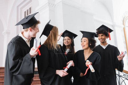 Positive multiethnic graduates looking at friends with diplomas