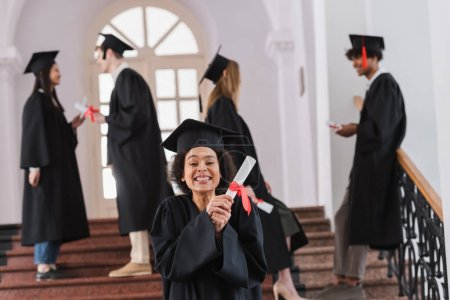 Photo for Happy african american graduate holding diploma near blurred friends in university - Royalty Free Image