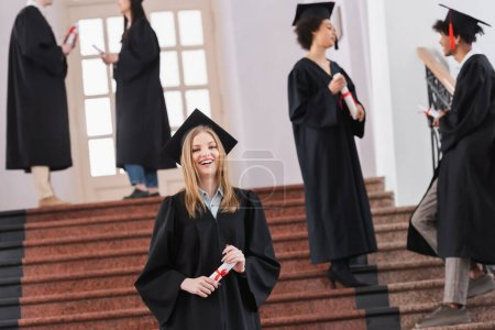 Happy student holding diploma during graduation in university