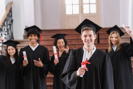 Photo for Smiling student in cap holding diploma near interracial friends on blurred background - Royalty Free Image