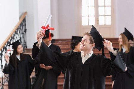 Photo pour Heureux baccalauréat à la recherche d'un diplôme près des étudiants multiethniques - image libre de droit