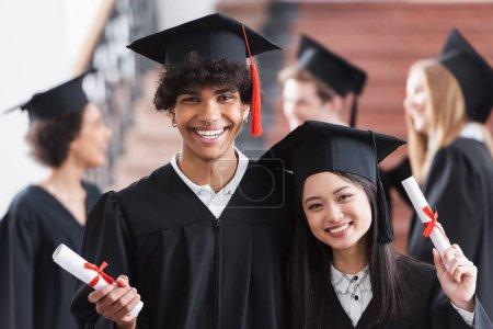 Afrikanisch-amerikanischer Junggeselle mit Diplom bei asiatischem Freund lächelnd