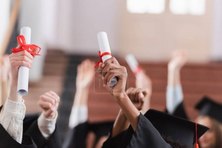 Cropped view of interracial students holding diplomas
