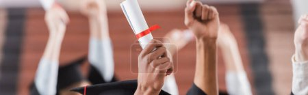 Cropped view of multiethnic students holding diploma near hands of blurred friends, banner