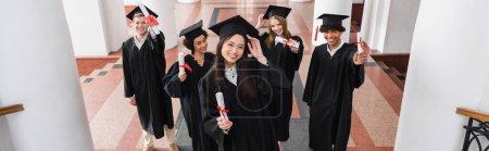 Photo pour Vue en angle élevé des étudiants multiethniques joyeux titulaires de diplômes, bannière - image libre de droit