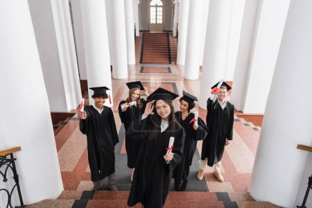 Photo for High angle view of cheerful asian graduate holding diploma near friends in caps - Royalty Free Image