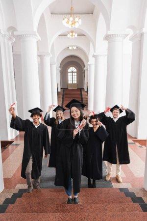 Photo pour Sourire asiatique diplômé tenant diplôme sur les escaliers près des amis à l'université - image libre de droit