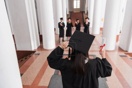 Photo for Back view of graduate in academic cap holding diploma near friends on blurred background - Royalty Free Image