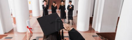 Back view of student in graduation cap holding diploma near blurred friends, banner