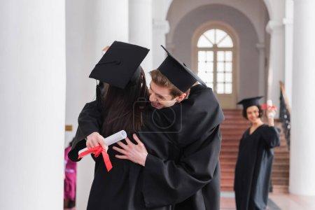 Photo pour Sourire diplômé avec diplôme étreignant ami - image libre de droit