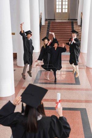 Photo pour Diplômés multiethniques excités avec des diplômes sautant amis proches sur le premier plan flou - image libre de droit