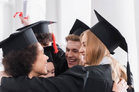 Photo for Smiling multiethnic students in caps hugging in university - Royalty Free Image