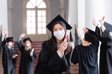 Photo for Asian bachelor in cap and medical mask holding diploma near blurred friends - Royalty Free Image