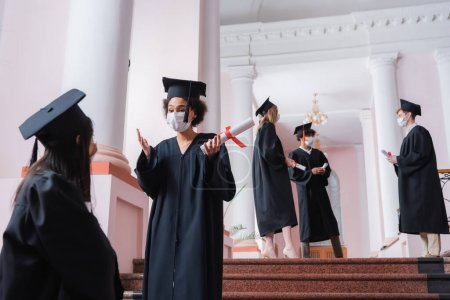 African american student in medical mask holding diploma and talking to asian friend