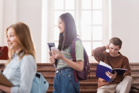 Student looking at notebook near multiethnic people on blurred foreground