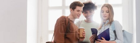 Interracial students with coffee to go and notebook standing near window, banner