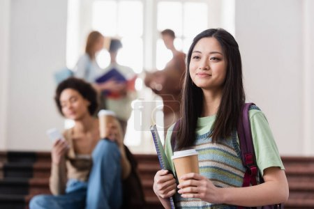 Asian student with coffee to go and notebook in university