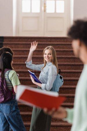 Photo pour Étudiant souriant avec cahier agitant la main à un ami flou - image libre de droit