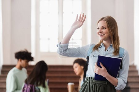 Happy student with notebook waving hand in hall of university