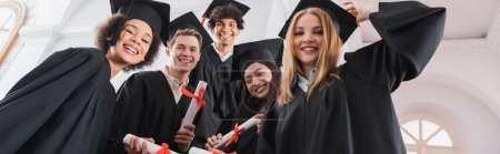 Photo for Low angle view of smiling interracial graduates holding diplomas, banner - Royalty Free Image