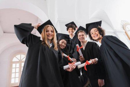 Photo pour Vue en angle bas des diplômés multiethniques avec des diplômes souriants à la caméra - image libre de droit