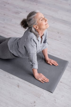 Photo for Pleased middle aged woman in cobra pose practicing yoga on mat at home - Royalty Free Image