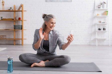 mujer de mediana edad sentada en una pose de loto en una esterilla de yoga y saludando con la mano mientras recibe una videollamada en un teléfono inteligente