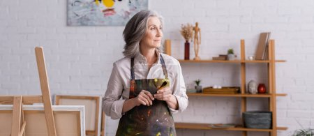 middle aged artist in apron holding paintbrush near easel, banner
