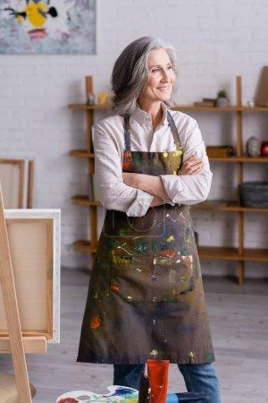 Photo pour Joyeux artiste d'âge moyen dans tablier debout avec les bras croisés près du chevalet - image libre de droit