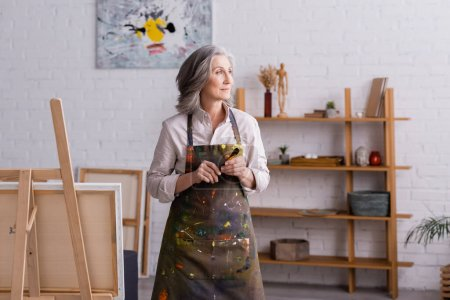 middle aged artist in apron holding paintbrush near easel