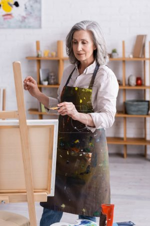 middle aged artist in apron holding paintbrush while painting at home