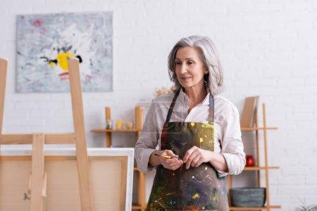 complacido artista de mediana edad en delantal con derrames sosteniendo el pincel y mirando el lienzo en caballete