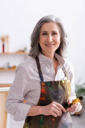 cheerful middle aged artist in apron with spills holding paintbrush
