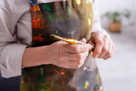 Photo for Partial view of middle aged artist in apron with spills holding paintbrush - Royalty Free Image