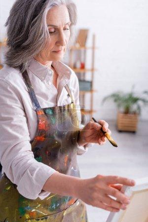 mujer de mediana edad sosteniendo el pincel cerca del caballete con lienzo