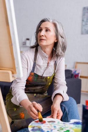 artista de mediana edad sosteniendo pincel y paleta con pinturas de colores mientras mira la lona