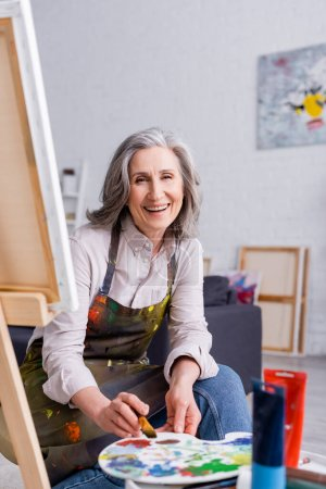 cheerful middle aged artist holding paintbrush and palette with colorful paints near easel with canvas