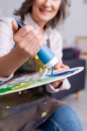 Photo for Cropped view of blurred middle aged woman holding tube with blue paint near palette - Royalty Free Image