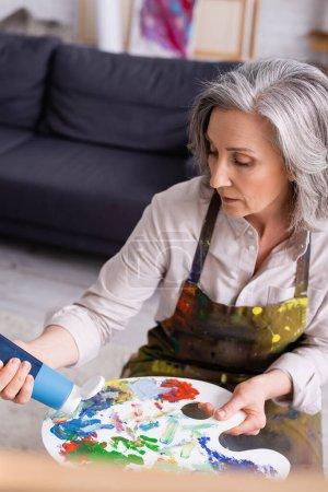 Frau mittleren Alters hält Tube mit blauer Farbe in der Nähe der Palette