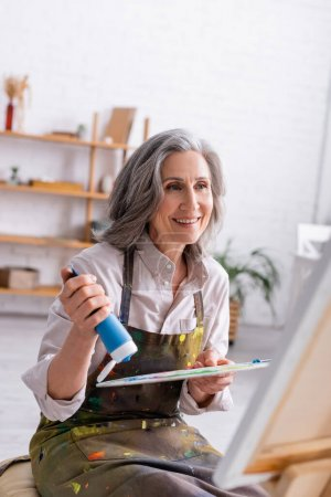 happy middle aged woman holding tube with blue paint near palette