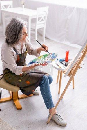 vista de ángulo alto de la mujer de mediana edad sosteniendo el pincel y la paleta con pinturas de colores