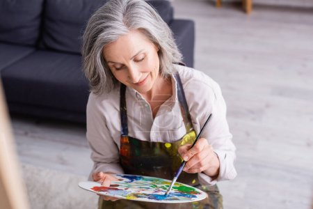 pleased middle aged woman in apron holding paintbrush and palette with colorful paints