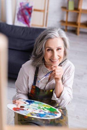 alegre mujer de mediana edad en delantal sosteniendo pincel y paleta con pinturas de colores