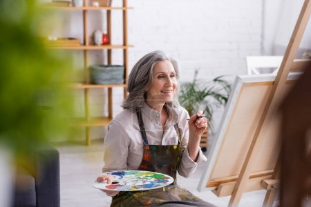Photo for Happy mature woman in apron holding paintbrush and palette near easel at home with blurred foreground - Royalty Free Image