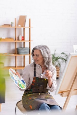 Photo for Cheerful mature woman in apron holding paintbrush and palette near easel at home with blurred foreground - Royalty Free Image
