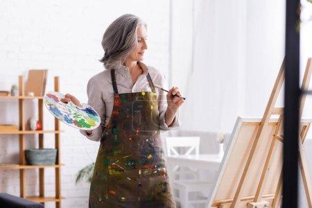 mujer madura alegre en delantal sosteniendo pincel y paleta cerca del caballete en casa