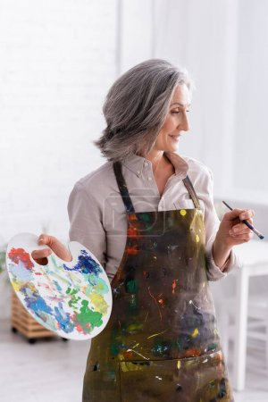 fröhliche reife Frau in Schürze mit Pinsel und Palette