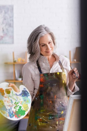 Photo for Cheerful mature woman in apron holding paintbrush and palette while looking at canvas - Royalty Free Image