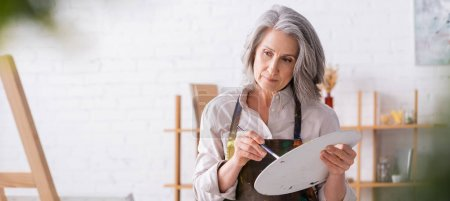 pensive mature woman in apron holding paintbrush and palette while looking at easel, banner